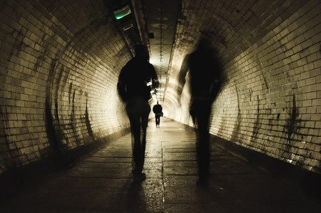 30507759 - two people walking in the dark tunnel