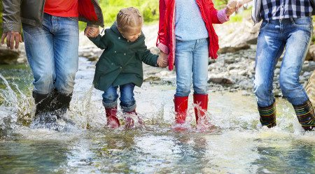 Stock photo of happy family splashing in a creek
