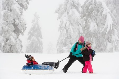 Stock photo of three children playing in the snow