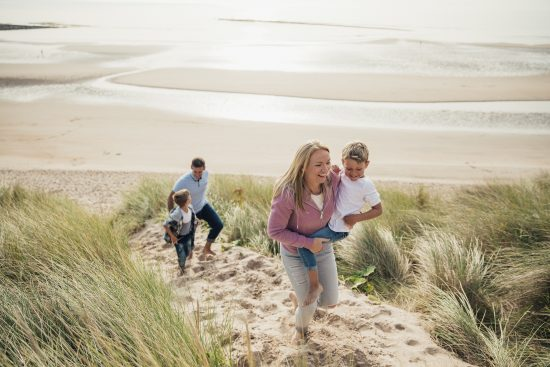 Active lifestyle stock photo showing a happy family on a walk at the beach