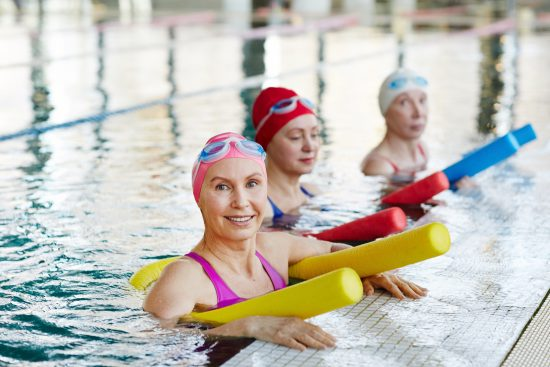Three women floating in a pool for an active lifestyle stock photo