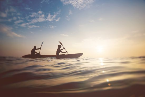 A couple kayaking at sunset creates a simple active lifestyle stock photo
