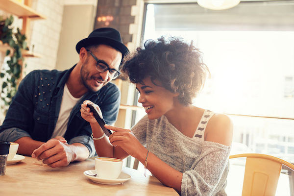 stock photo showing a couple using a cell phone to stay connected in a coffee shop
