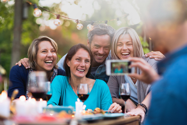 Stock photo showing friends posing for a photo at a dinner party