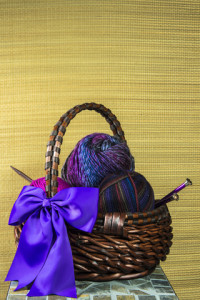 http://www.dreamstime.com/royalty-free-stock-images-basket-colorful-purple-pink-variegated-yarn-knitting-needles-visible-large-purple-bow-textured-straw-mat-as-background-space-text-image29724839