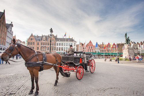 BRUGES, BELGIUM - MAY 17: The Carriage on the Grote Markt and Belfort van Brugge in background on 17 May 2014