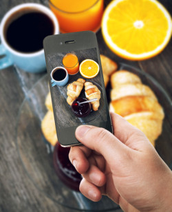 Hand with smartphone taking food photo of fresh breakfast with coffee and croissants