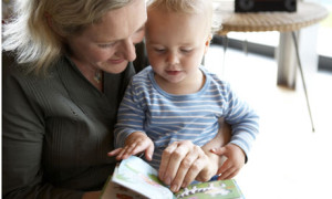 Older mother reads to her baby son